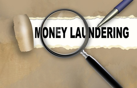 money laundering: word MONEY LAUNDERING and magnifying glass with pencil Stock Photo