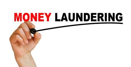 Hand underlining money laundering with red marker