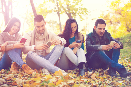 cell phone addiction: Group of young people in the park with cell phones Stock Photo