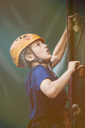 recreational pursuits: Little boy rock climbing Stock Photo