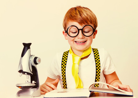 sholders: Happy little boy with a book and a microscope.