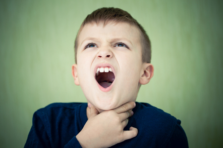 sore throat: Little boy with a sore throat, on the green background. Holding his neck and grimacing in pain.