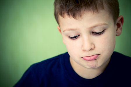pout: Sad little boy looking down on green background. Stock Photo