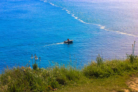 Green grass against a background of blue ocean in summer and a little boat on the horizont 免版税图像