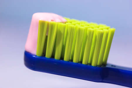 Blue toothbrush with green bristles close-up, pink toothpaste. Hygiene and care Stok Fotoğraf