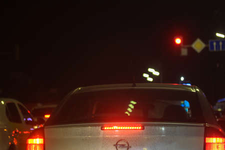 Grey dirty Opel car standing in traffic at red traffic lights at night, signs indicating road ahead
