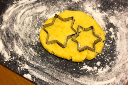 Star-shaped cookie cutter molds and freshly kneaded yellow dough inside, black cutting board sprinkled with white flour. Homemade wholesome pastries