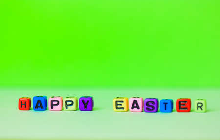 Happy Easter multicolored words written with wooden alphabet letters on a bright green background. Minimalistic Easter background. Greeting card for Christian or Catholic Easter. Place for text flatly Фото со стока