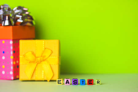 Happy Easter multicolored words written with wooden alphabet letters on a bright green background. Gift boxes in the background. Greeting card for Christian or Catholic Easter. Place for text. Flatly.