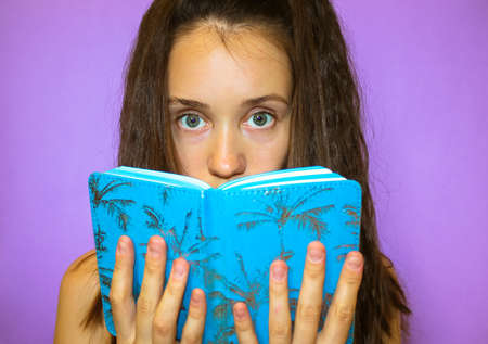 A beautiful long-haired gray-eyed brunette student girl is holding a blue book, a notebook, covering face with it. Young woman studying, reading, preparing for a session. Surprise, consternation.