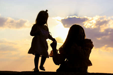 Silhouette of a young mother with infant baby girl against a sunset yellow sky at summer. Mom holding kid by the hand. First step. The joys of motherhood. Relationship between parents and children.