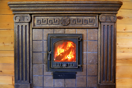 burning fireplace: Design Burning fireplace with cast iron door near the wooden wall.