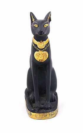 Statuette of a seated divine Egyptian cat with gold decorations. White background.