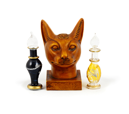 cat goddess: Statuette of the Egyptian head of the divine cat and two elegant bottle with Egyptian aromatherapy oils and perfume. White background.