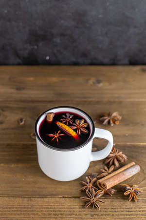 A mug of hot red mulled wine with spices, cinnamon, orange and star anise. Christmas hot drink. Holiday atmosphere