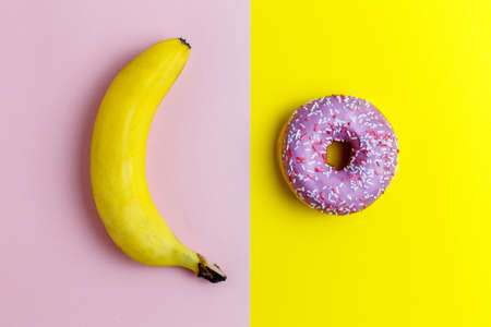 Healthy vs unhealthy food, dieting concept. Pink donuts, doughnut with sweet sprinkles on yellow and a banana isolated on pink color background