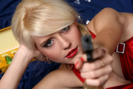 Beautiful young woman holding gun, focus on face