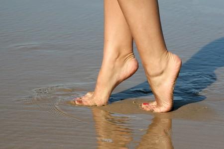 Beautiful female feet on sea sand photo