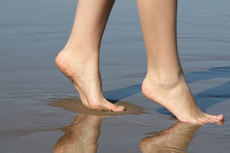 Beautiful female feet on sea sand Stock Photo