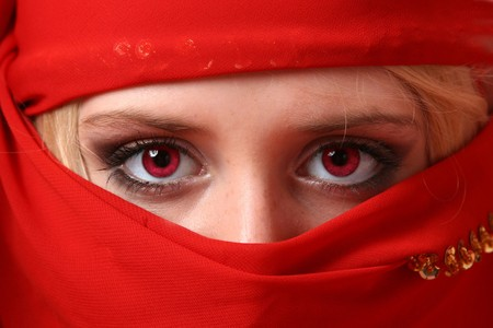 Young woman with red eyes wrapped in a red headscarf photo