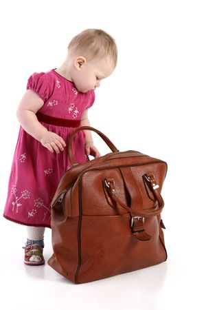 Toddler opens an old travel bag Stock Photo - 5625590