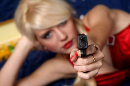 female assassin: Beautiful young woman holding gun, focus on gun Stock Photo