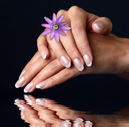 Beautiful woman hand with french manicure, over black background Stock Photo