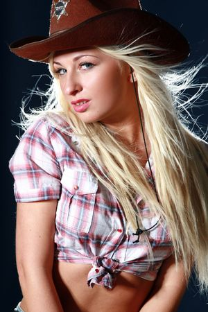 Blonde rodeo girl wearing a cowboy hat on dark background photo