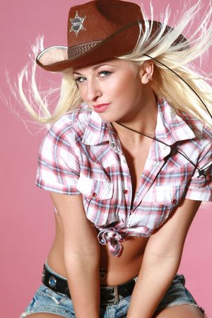 Close-up portrait of beautiful rodeo girl in cowboy hat on pink background Stock Photo - 6229787