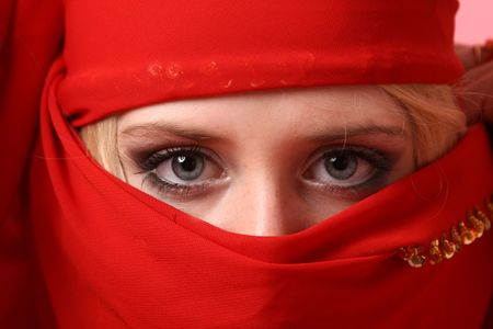 Beautiful girl behind an red scarf used like a burka photo