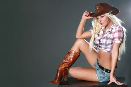 Portrait of a beautiful sexy rodeo girl on dark gray background