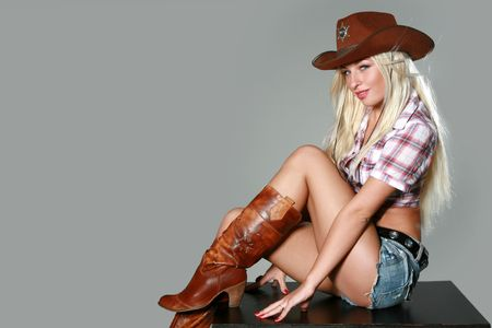 Portrait of a beautiful sexy rodeo girl on gray background