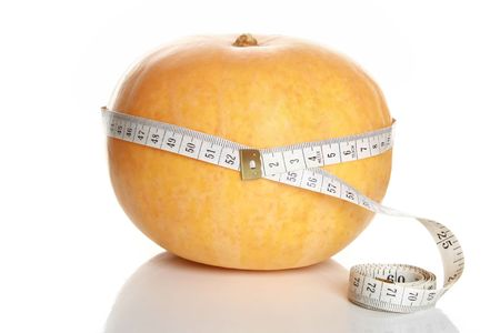 Tape measure wrapped around pumpkin, on white background