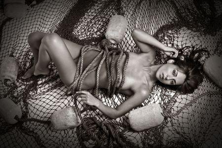 Beautiful naked girl lies in fishing nets Stock Photo - 6374902