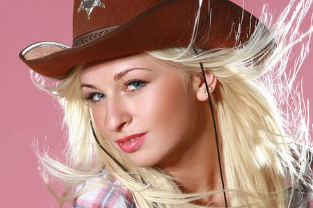 Sexy woman with cowboy hat, on pink background photo