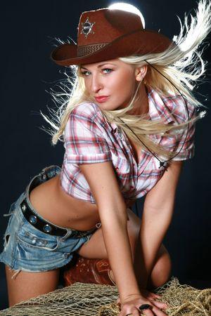 Pretty woman with cowboy hat. Studio shot photo