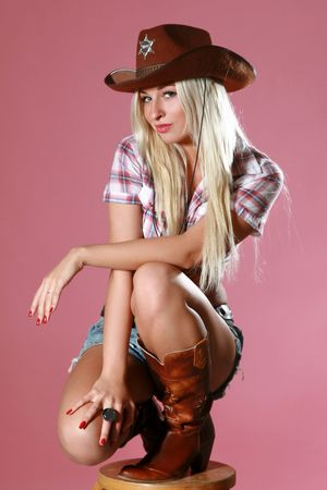 Pretty girl with cowboy hat on pink background Stock Photo