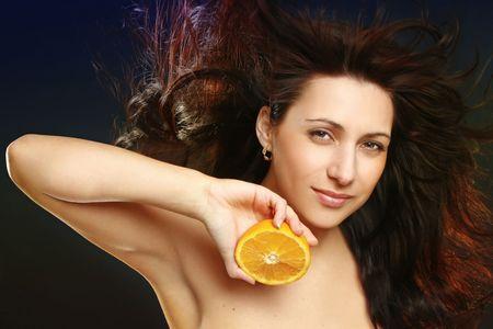 Beautiful cheerful woman with fresh orange near her face photo
