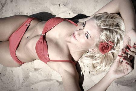 Beautiful young woman in red bikini on beach (sepia colored)