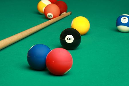 Billard table with a couple of balls and cue photo