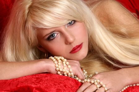 Beautiful and sexy blonde girl close-up portrait on red background