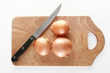 bisected: Onions on a chopping board. Nearby a kitchen knife Stock Photo
