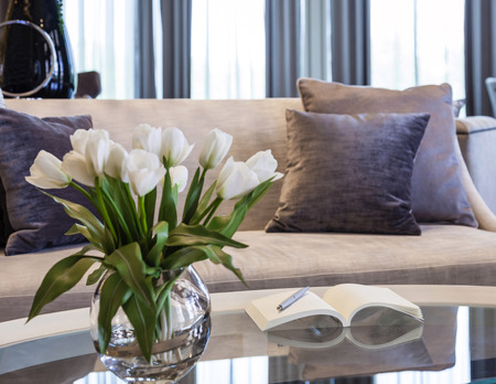 Living room sofa with book and flower Фото со стока
