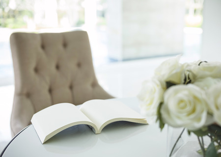 Book on table with white rose interior decoration photo