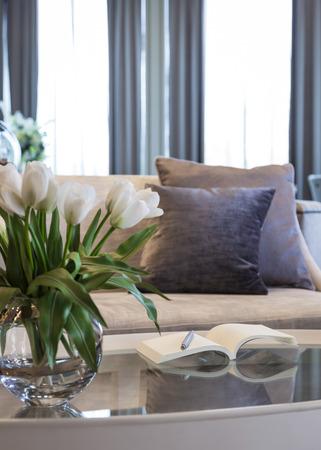 buen vivir: Sala de estar con sofá y Almohadas libro en la mesa y la decoración de la flor del tulipán Foto de archivo