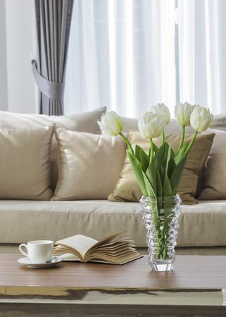 decoracion mesas: Sof� de la sala con el caf� de la flor y el libro en la mesa Foto de archivo