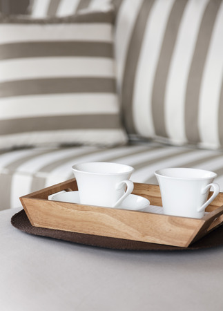 hotel room: Coffee cup in wooden tray on table with sofa background Stock Photo