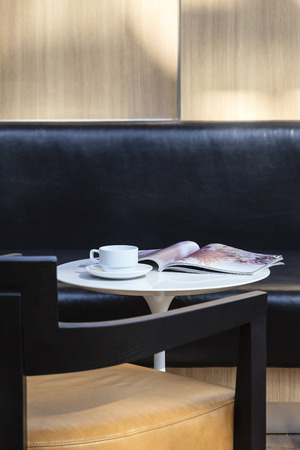 Coffee cup and magazine on table with sofa seat Interior Decoration