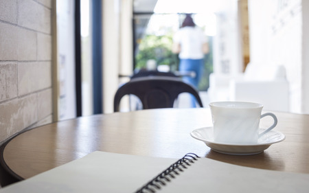 Book and coffee cup on table with Restaurant cafe Interior background Фото со стока