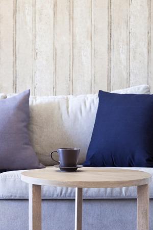buen vivir: Sofá con la almohadilla en la sala de estar con la taza de café en la mesa de madera
